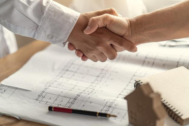 Accordo di stretta di mano dei clienti con l'appaltatore per la costruzione di case