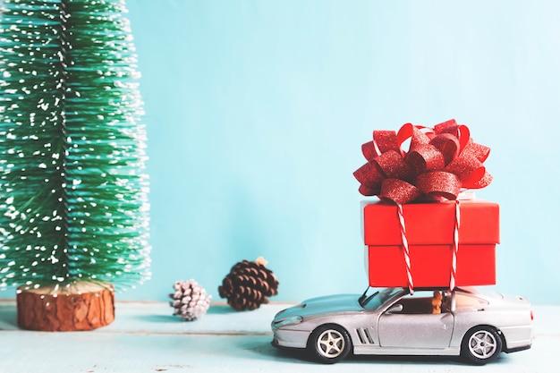 Accumulazione dei giocattoli di festa di natale con il contenitore di regalo sull'automobile. effetto filtro vintage