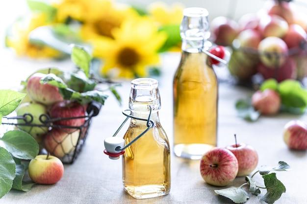Aceto di mele. bottiglia di aceto di mele biologico o sidro su fondo in legno. alimenti biologici sani