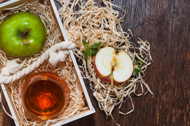 Aceto di mele e mela verde in cassa di legno con carta rasata sulla tavola di legno