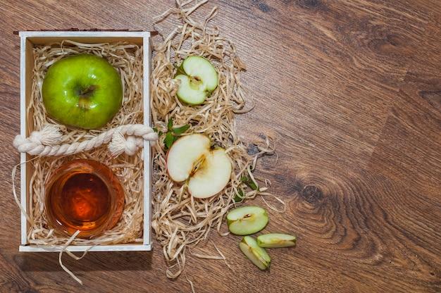 Aceto di sidro di apple con la mela verde in cassa di legno sulla tavola di legno