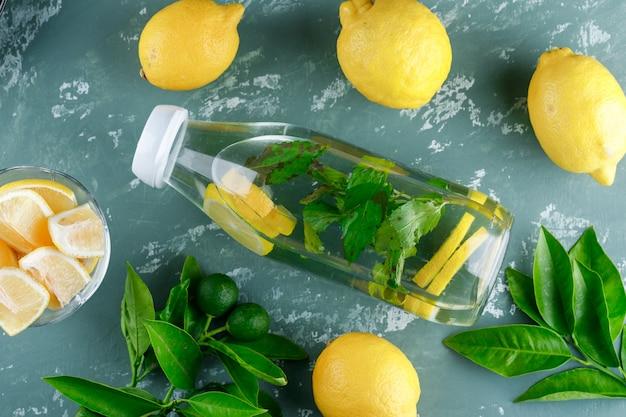 Acqua al limone con menta, foglie in una bottiglia sulla superficie dell'intonaco