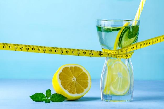Acqua al limone in un bicchiere, limone succoso, menta e nastro di misurazione,