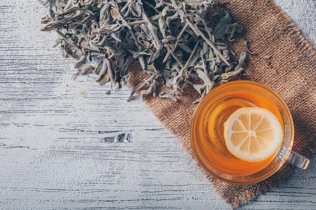 Acqua arancione con la vista superiore delle erbe del tè su una tela di sacco e su un fondo di legno grigio. spazio per il testo