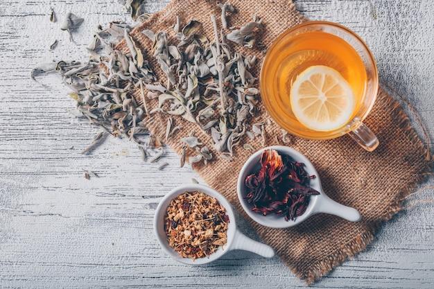 Acqua arancione di vista superiore con le erbe del tè su tela di sacco e su fondo di legno grigio. spazio orizzontale per il testo