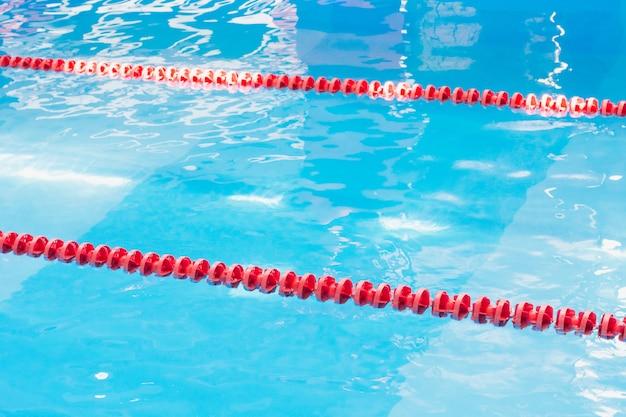 Acqua blu della piscina e indicatore di corsia di nuoto rosso