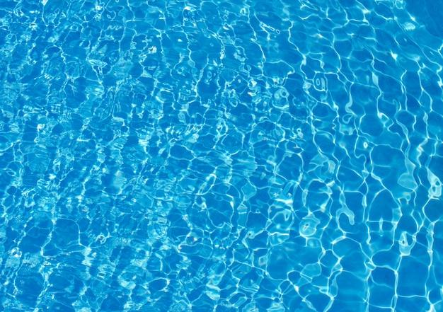 Acqua blu dello stagno con i riflessi del sole