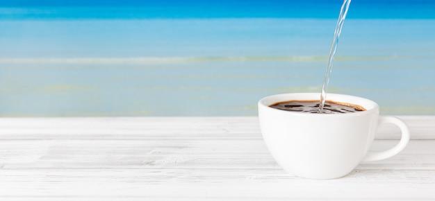 Acqua calda di versamento nella tazza di caffè sulla tavola di legno bianca con il fondo blu luminoso del mare