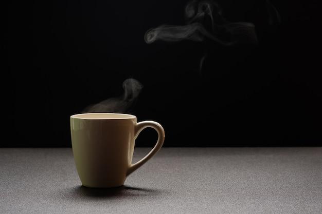 Acqua calda sulla tavola di legno, vapore della bevanda e spazio della copia, fuoco selettivo. concetto di bevanda calda