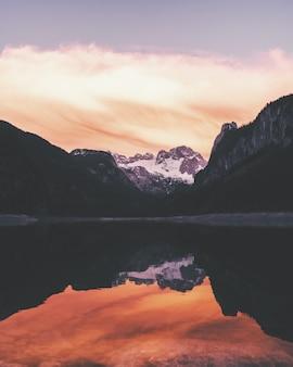 Acqua che riflette la riva circondata da montagne sotto un bel cielo