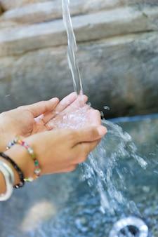 Acqua che scorre nelle mani in strada