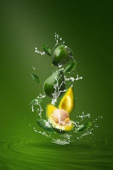 Acqua che spruzza sull'avocado verde affettato fresco sopra verde.