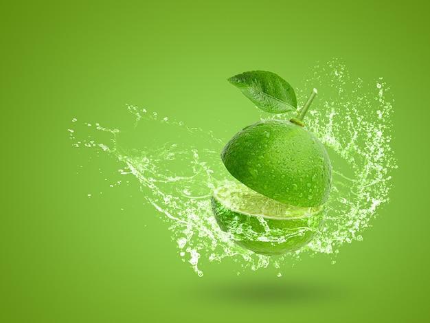 Acqua che spruzza sulla calce verde fresca isolata su fondo verde