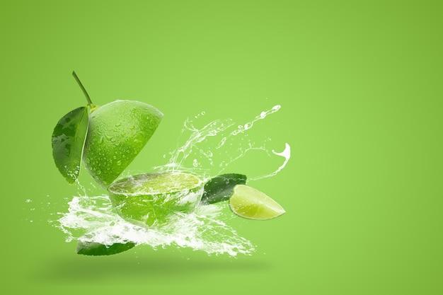 Acqua che spruzza sulla calce verde fresco isolato su sfondo verde