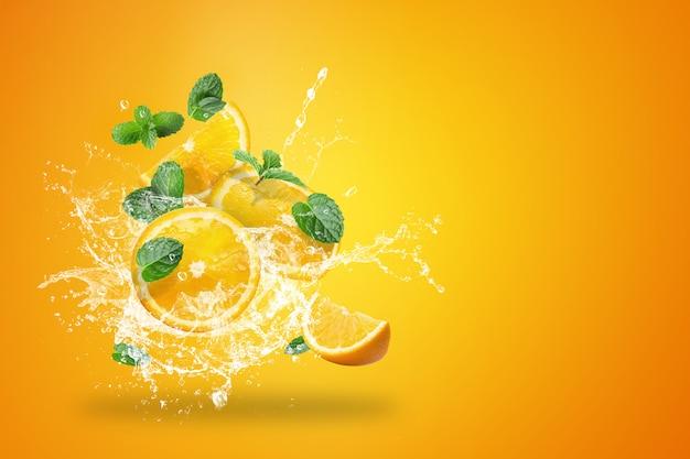 Acqua che spruzza sulla frutta fresca affettata delle arance