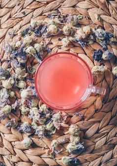 Acqua colorata rossa di vista superiore su fondo trivet con le erbe del tè verticali