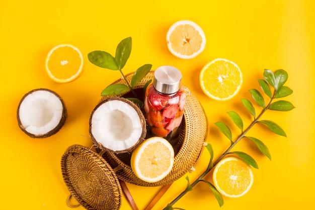 Acqua con fragole, arance, limoni e noci di cocco sul giallo con una borsa di paglia
