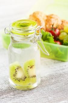 Acqua con kiwi e scatola per il pranzo verde