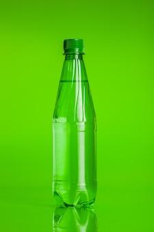 Acqua cristallina in una bottiglia su sfondo verde