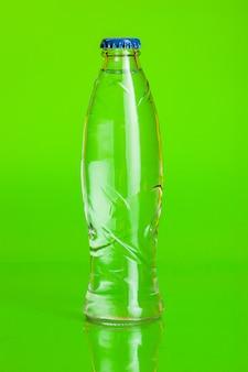 Acqua cristallina in una bottiglia su verde