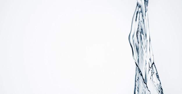 Acqua del primo piano dinamica su fondo bianco con lo spazio della copia