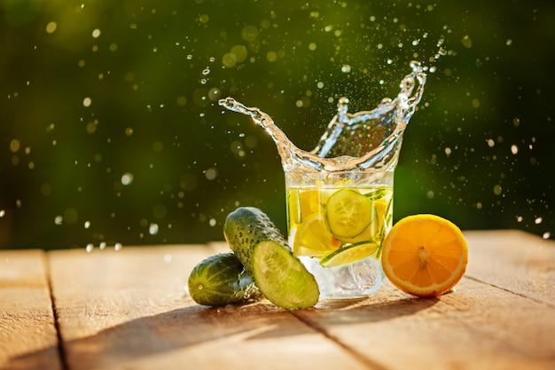 Acqua della disintossicazione con il limone ed i cetrioli con spruzzata sulla tavola di legno e sul fondo verde della natura
