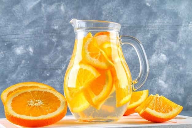 Acqua detox arancio in una brocca su uno sfondo grigio cemento. cibo sano, bevande