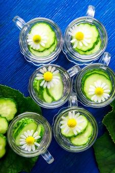 Acqua di cetriolo in sei piccoli barattoli di vetro su superficie blu