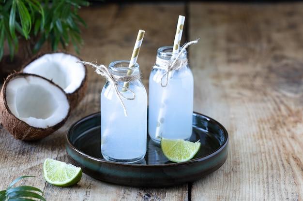 Acqua di cocco fresca in bottiglia di vetro sul tavolo. bevanda vegetariana. copia spazio