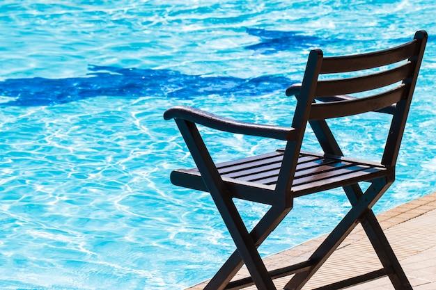 Acqua di lusso blu della piscina delle sedie per rilassamento sulla vacanza di viaggio di estate sulla spiaggia.