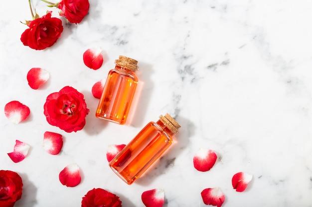 Acqua di rose profumata in bottiglia di vetro e piccole rose rosse con petali.
