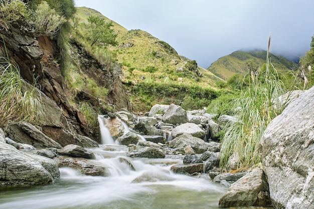 Acqua di ruscello che investe pietre con vegetazione sulla riva del fiume