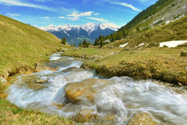 Acqua di un ruscello alpino che scorre in montagna e cime innevate