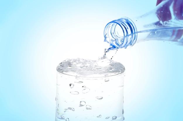 Acqua di versamento dalla bottiglia in vetro su fondo blu