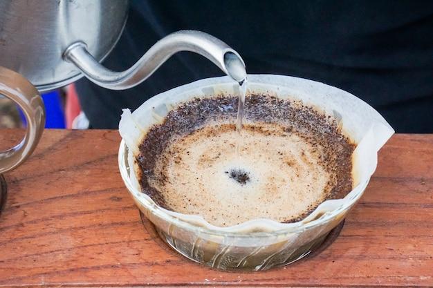 Acqua di versamento per immergere il caffè fresco per preparare un caffè fresco a mano.
