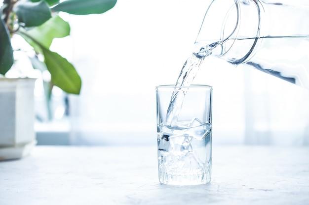 Acqua di versamento su vetro sulla tavola bianca