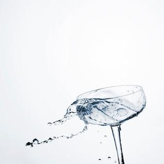 Acqua dinamica del primo piano in vetro trasparente con lo spazio della copia