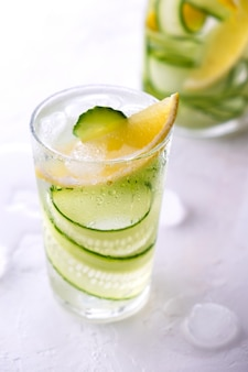 Acqua disintossicante infusa fredda e rinfrescante con limone e cetriolo in un bicchiere. limonata aromatizzata fatta in casa