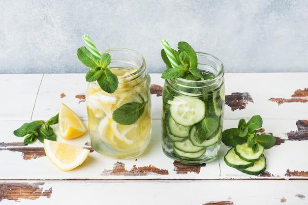 Acqua dolce in barattolo con limone, cetriolo e menta sul tavolo di legno.