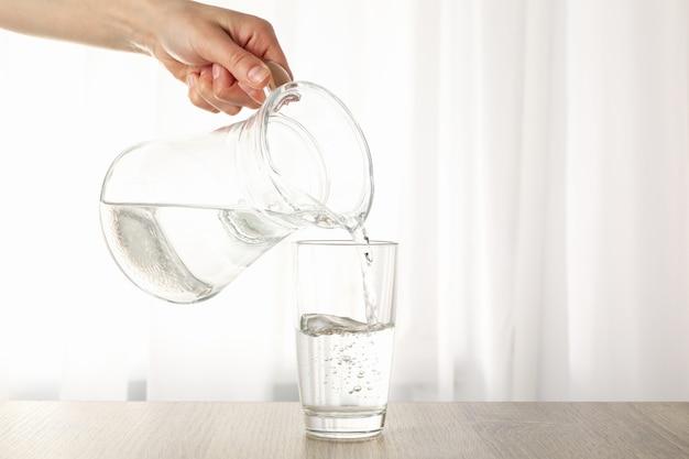 Acqua dolce purificata di versamento dalla brocca in vetro sulla tavola di legno