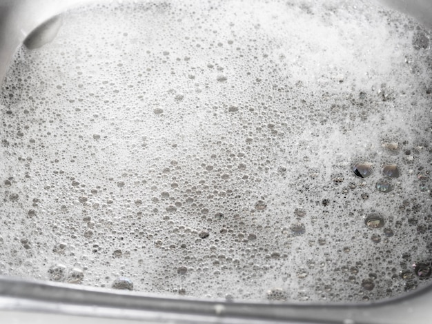 Acqua e schiuma saponata dopo aver lavato i piatti nel lavello della cucina in zinco