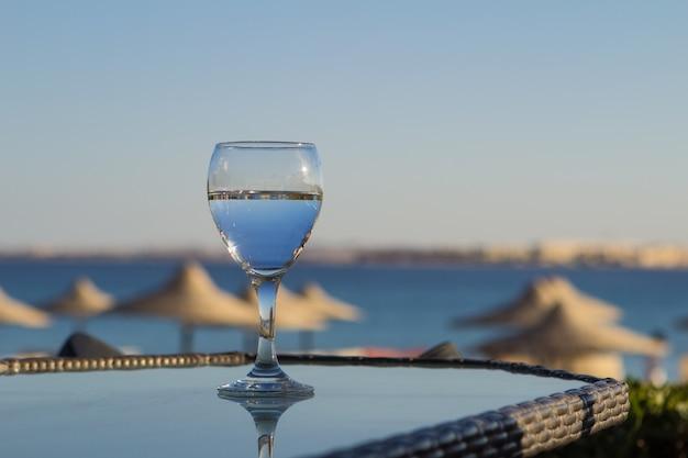 Acqua fredda fresca in un bicchiere con una cannuccia sul tavolo in mare.