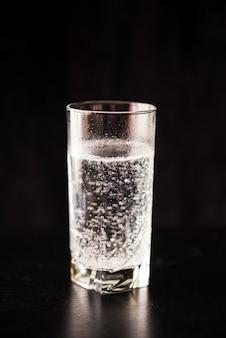 Acqua gassata in un bicchiere su un tavolo nero e sfondo nero.