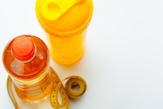 Acqua in bottiglia per una vita sana e nastro di misurazione su uno sfondo bianco