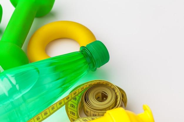 Acqua in bottiglia per vita sana e nastro di misurazione sopra un bianco