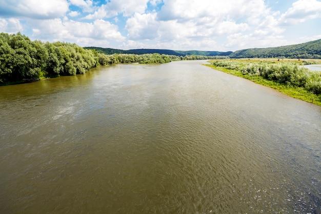 Acqua in largo fiume in estate con alberi verdi sulle rive