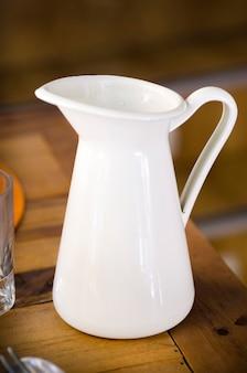 Acqua in metallo bianco / lanciatore di latte in un bar sopra legno