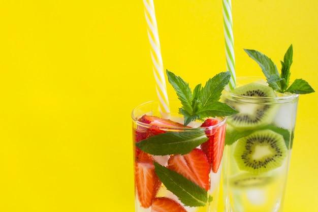 Acqua infusa o limonata con fragole e kiwi in bicchieri