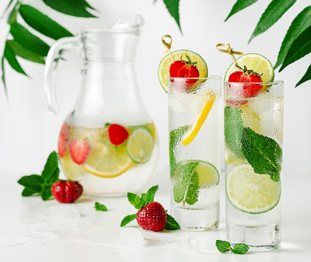 Acqua infusa rinfrescante con calce, limone, menta e fragola su bianco. bere sano