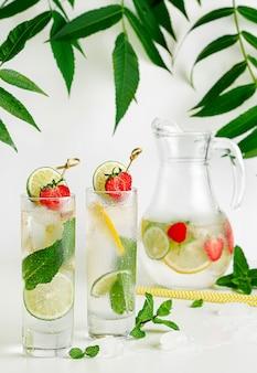 Acqua infusa rinfrescante con calce, limone, menta e fragola su bianco. copia spazio